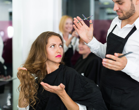 hairdressing scissors: Hairdresser quarrels with the female client in the barbershop