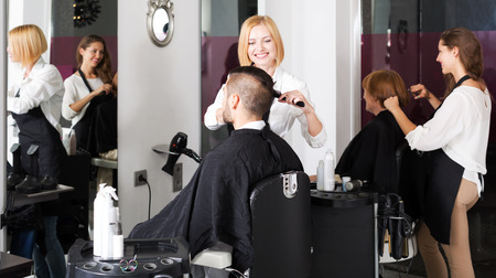 barber: Adult man cuts hair and female barber at the hair salon
