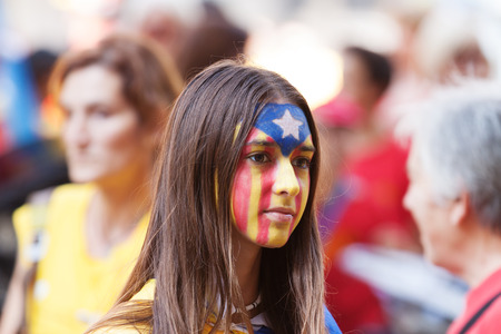 independency: BARCELONA, SPAIN - SEPTEMBER 11, 2014: Unidentified Catalan young woman making Catalan Flag on face and waiting  rally to National Day of Catalonia, Barcelona Editorial