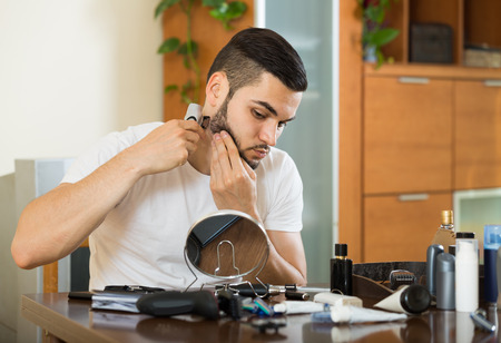 trimmer: positive american man looking at mirror and shaving beard with trimmer