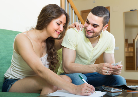 budget: Happy smiling young couple calculating the family budget at home