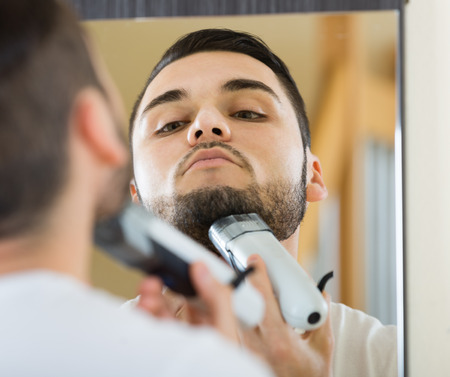 25s: russian man looking at mirror and shaving beard with trimmer