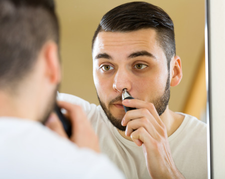 trims: portrait handsome young man trims nose and ears hair at home