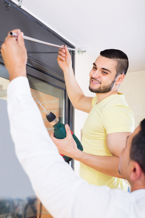 corbel: Two positive male adults putting corbel at residential kitchen Stock Photo