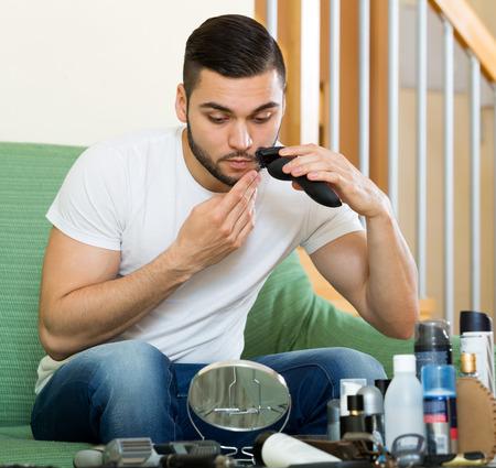electric razor: Handsome man shaving moustache by electric razor