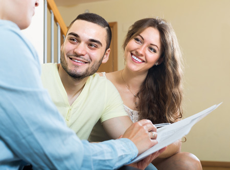 private insurance: Young couple discussing details of private insurance with agent at home Stock Photo