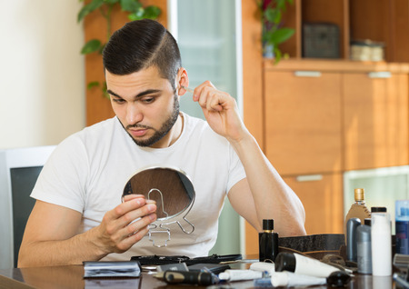 plucking: Adult man plucking hair from his nose with pliers Stock Photo