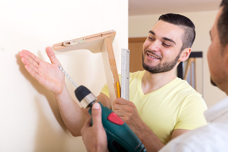 work from home: Two happy skilled men doing maintenance work at home Stock Photo