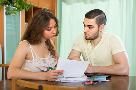 banking concept: Young married couple sitting at the table and calculating the family budget Stock Photo