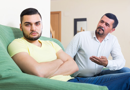 odds: Portrait of two male adults sitting on couch and being at odds at home