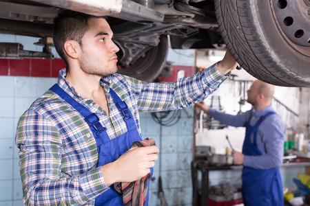 hard work: Two serious car mechanics checking up pressure in tires at workshop Stock Photo