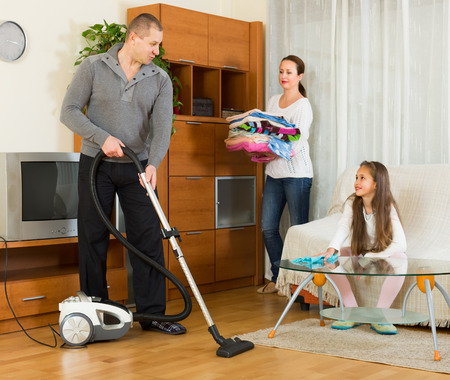 tidying up: Positive family of three tidying up a room all together. Focus on man