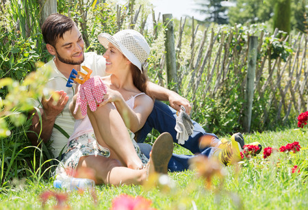 floriculturist: Smiling family with gardening tool in their backyard garden Stock Photo