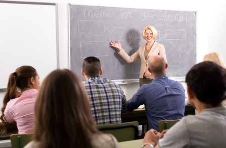 mixed age: Female professor teaching class of mixed age students at refresher courses