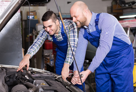 journeyman: Portrait of two professional car mechanics working together at garage and smiling