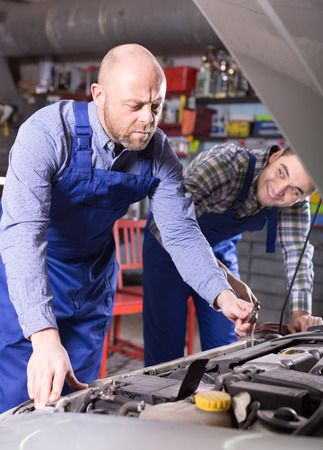 two car garage: Two professional car mechanics working together at garage Stock Photo