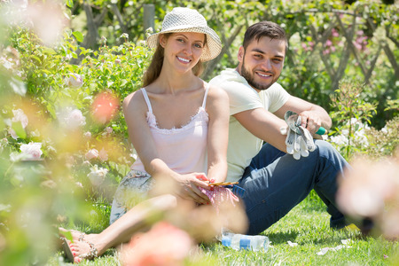 gardening: Happy young smiling couple resting on the grass after gardening