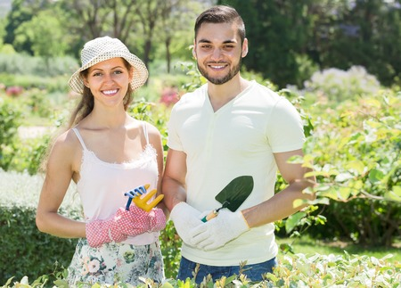 floriculturist: Young couple gardening together  in garden