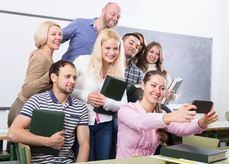 cohesive: smiling students of different age doing group selfie on smartphone Stock Photo