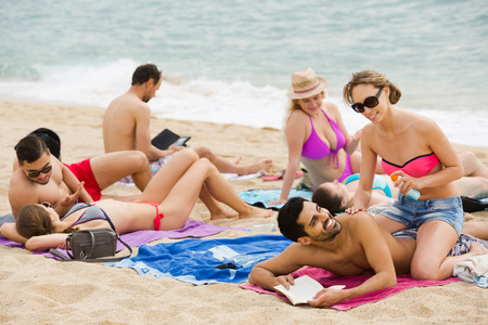 european people: Group of happy european people laying on sand at beach and sunbathing Stock Photo
