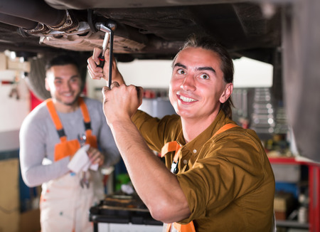 exhaust system: Serviceman at a dealership repairing exhaust system on a lifted up car Stock Photo