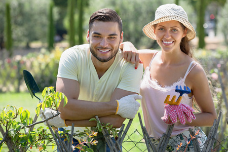 horticultural: Happy couple in gloves with horticultural sundry in garden Stock Photo