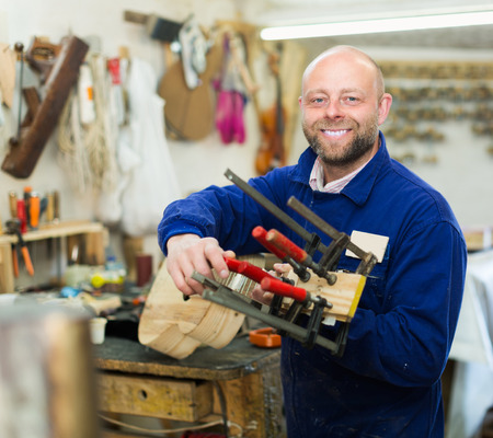 woodworker: Portrait of happy adult professional woodworker on lathe at musical instrument workroom Stock Photo