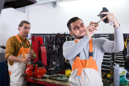 toiling: Two professional workers in uniform at workshop. Selective focus