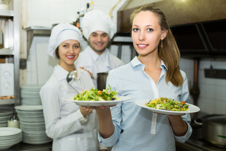 obreros: Beautiful young blonde female waiter taking dish from kitchen