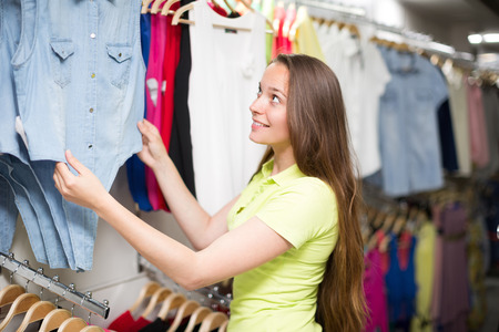 clothing store: Smiling woman shopping blouse in clothing store