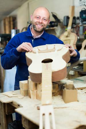 buildup: Portrait of positive guitar maker holding unfinished guitar at workshop