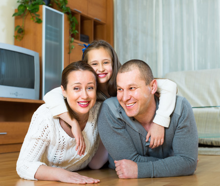 Happy little girl with parents posing at floor and smiling