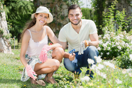 floriculturist: Happy family seedling garden plants in garden at sunny day