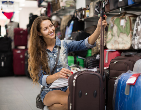 portmanteau: smiling russian woman choosing luggage bag in shop