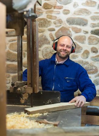 woodcutting: Positive smiling craftsman working on a woodcutting machine at guitar workshop