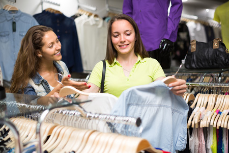 blouses: Smiling young woman with friend choosing blouse in clothing store