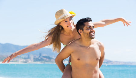 parejas jovenes: Amorosa pareja de adultos que se divierten en la orilla del mar en un d�a soleado