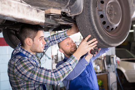 two car garage: Two serious professional car mechanics checking up pressure in tires at garage
