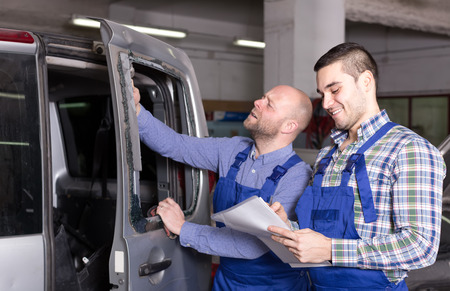 rear end: Insurance agent and mechanic examine a car with rear end damage and calculate loss Stock Photo