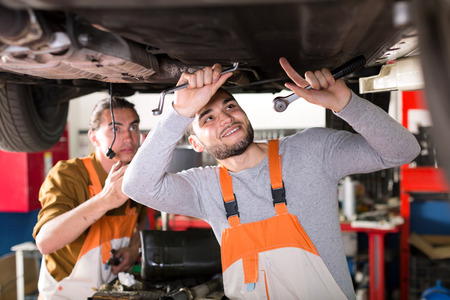 hábil: Skilled smiling mechanics in coveralls working under a lifted up car