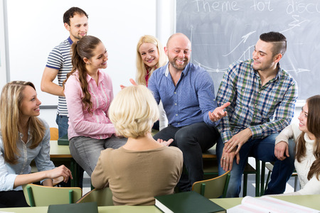 adult education: Male teacher and adult students during break in classroom Stock Photo