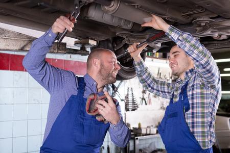 tire repair shop: Two smiling american  people fixing car tire leak Stock Photo