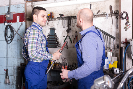 toiling: Two professional servicemen in a repair shop Stock Photo