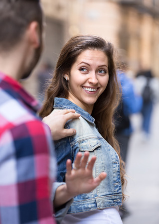 stranger: Happy woman smiling back to a stranger who is picking her up on a street Stock Photo