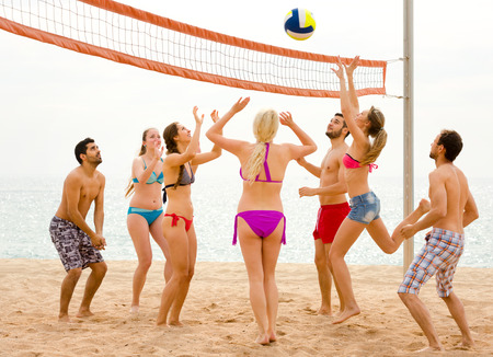freetime activity: Group of mixed gender tourists playing beachvolley near the sea Stock Photo