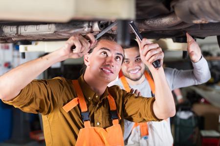 serviceman: Professional smiling serviceman repairing car of client