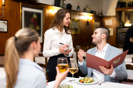 couple dining: Beautiful couple dining in a restaurant while happy waitress is taking their order