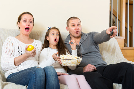 tv show: Parents and daughter watching TV show together at home. Focus on  woman