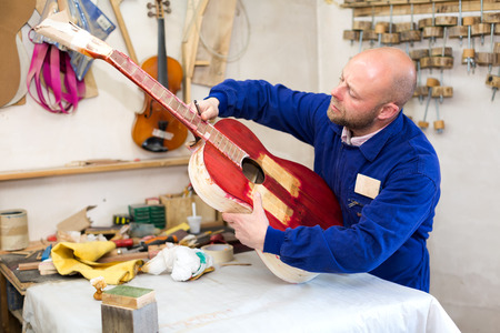 workplace wellness: Portrait of professional guitar maker at his workplace with an instrument indoors Stock Photo