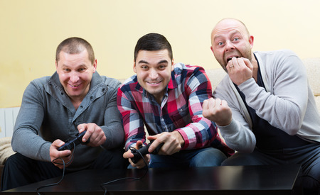 Happy adult friends relaxing with video game and laughing at